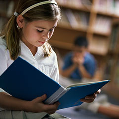 Girl reading a book in school library